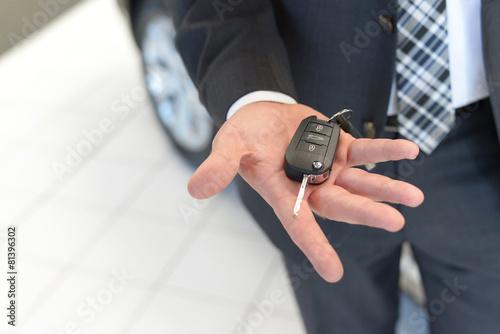 Fotografie, Obraz  Verkäufer hält neuen Autoschlüssel in der Hand