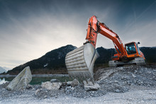 Heavy Organge Excavator With Shovel Standing On Hill With Rocks