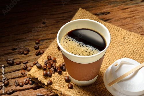 obraz lub plakat Paper cup of coffee and coffee beans on wooden table