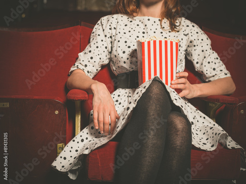 Fotografía  Young woman sitting in movie theater with popcorn