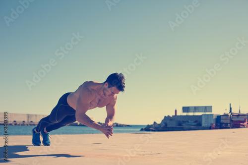 Fotografía  Muscular athlete doing jumping push-ups outdoors (intentional vi
