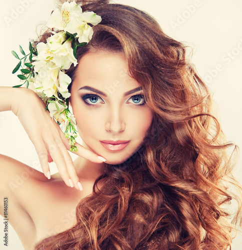 Spring freshness. Girl with delicate pastel flowers in hair Plakat
