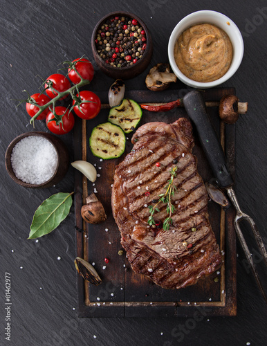 Fotografering  Beef rump steak on black stone table