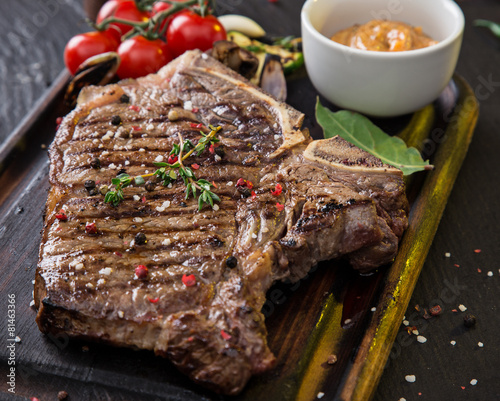 Beef t-bone steak on black stone table Canvas