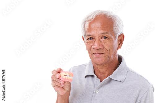 Photo old senior man with hand holding denture