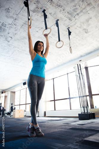 Zdjęcie XXL Piękna młoda kobieta robi ćwiczenia na pierścienie gimnastyczne
