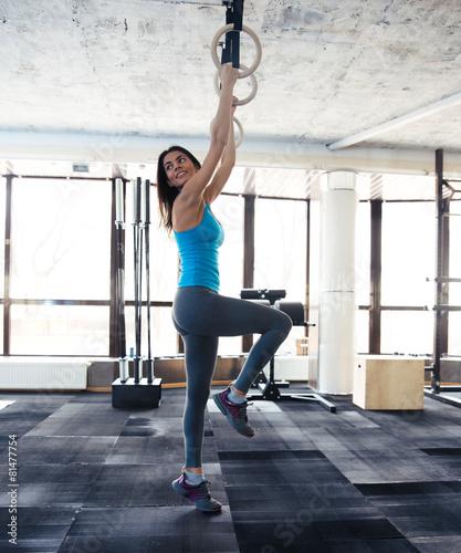 Zdjęcie XXL Uśmiechnięta kobieta pracuje na gimnastyczne pierścienie