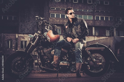 Fotografie, Obraz  Biker and his bobber style motorcycle on a city streets