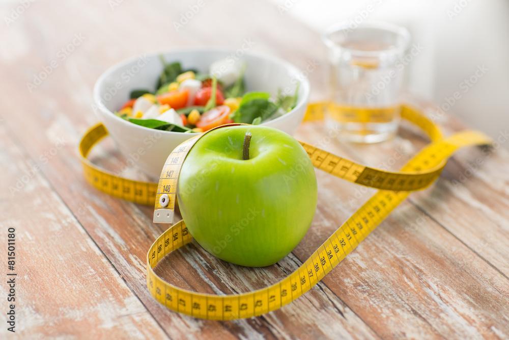 Fototapeta close up of green apple and measuring tape