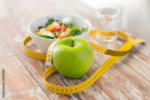 Fotografia  close up of green apple and measuring tape
