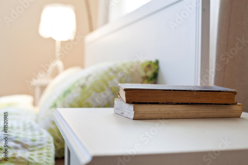 bedroom with books on nightstand Canvas Print