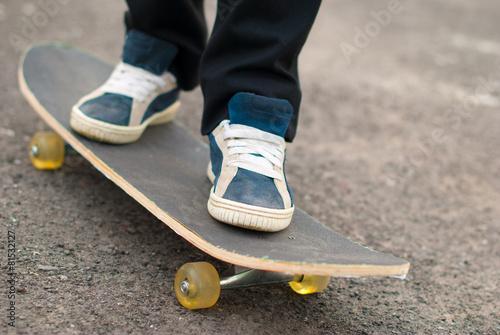 Fotografie, Obraz  Skateboarder feet in sneakers on a skateboard.
