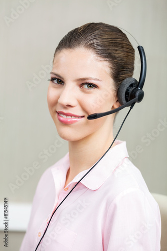 ea262feef0e Smiling Female Call Center Employee Using Headphones. By Tyler Olson