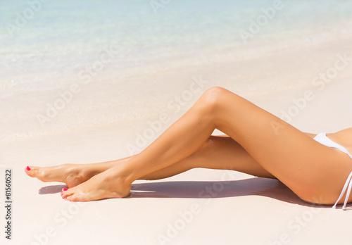 Fotomural Beautiful slim woman's legs on the beach