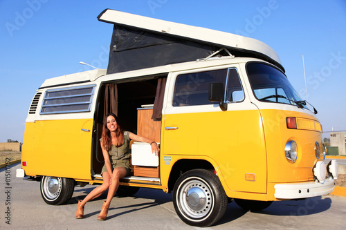 Model sitting in a yellow camper with a folding roof Poster