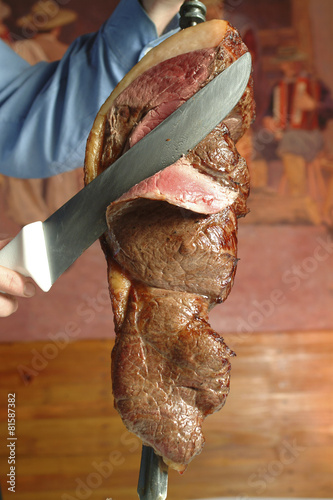 Fotografie, Obraz  Waiter cutting meat in typical Brazilian barbecue