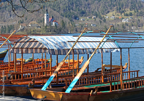 Poster Stadion rowboats moored on the shore of Lake Bled in Slovenia and the Ch