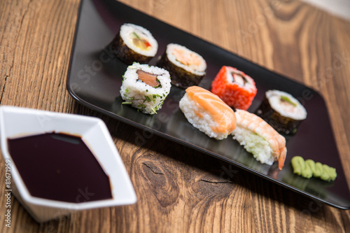 Poster Sushi bar Sushi pieces collection with bamboo chopsticks, isolated on wooden table