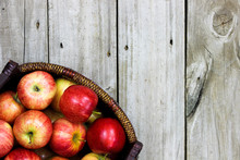 Basket Of Red Apples On Rustic Wood Background