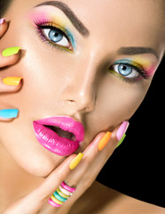 Fototapeta Beauty girl face with vivid makeup and colorful nail polish