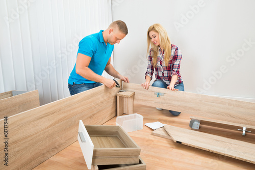 Fotografie, Tablou  Couple Assembling Wooden Furniture
