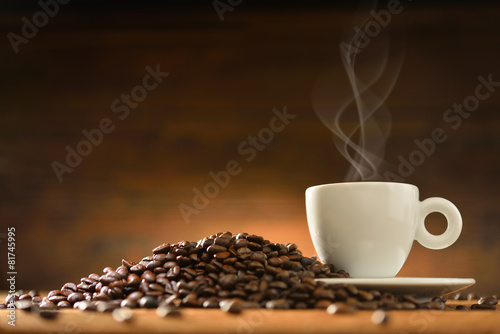Spoed Foto op Canvas koffiebar Cup of coffee with smoke and coffee beans on wooden background