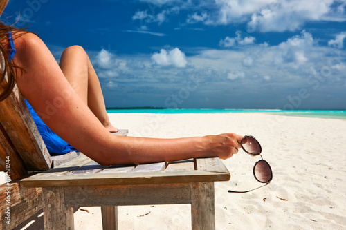 Deurstickers Ontspanning Woman at beach holding sunglasses