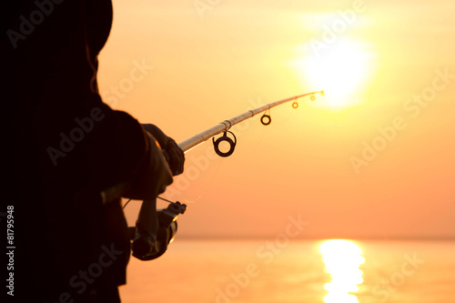 Tuinposter Vissen young girl fishing at sunset near the sea