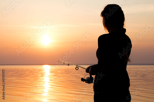 Fotobehang Vissen silhouette of a girl on the bank of the river with a fishing rod