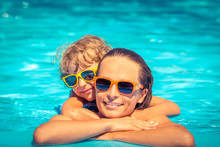 Child And Woman Playing In Swimming Pool