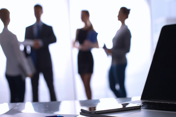 Laptop  computer on  desk ,  businesspeople standing in the