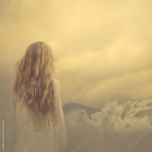 girl in a dress stands in the clouds over the mountains Wall mural