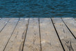 Wooden deck by water, background with copy space
