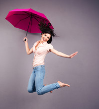 Happy Young Woman Jumping With...