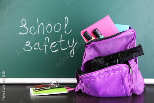 Fotografia, Obraz  Gun in school backpack on wooden desk, on blackboard background
