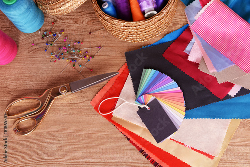 Poster Tissu Samples of colorful fabric on wooden table, top view