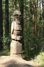 The Sculpture Is Made Of Wood. Wooden Idol In The Forest.