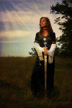 Mystical Medieval Woman  Standing  With A Sword On A Wild Meadow