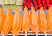 Many Pieces Of Cantaloup, Strawberry And Melon On Wood Sticks On
