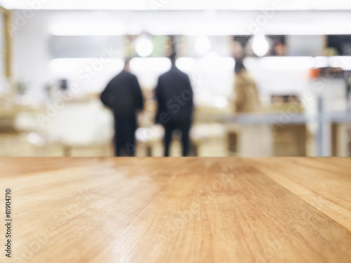Staande foto Industrial geb. Table Top with Blurred people in shop interior background