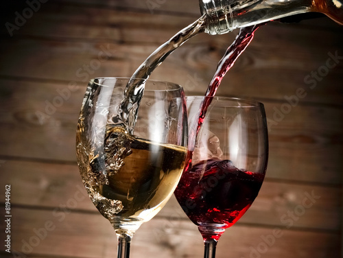 Red and white wine pour in two glasses Poster