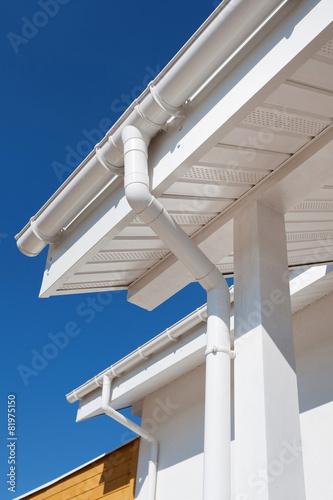 Valokuva  New rain gutter on a white home against blue sky