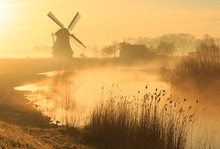 Windmill During A Foggy, Yellow Sunrise In The Countryside.