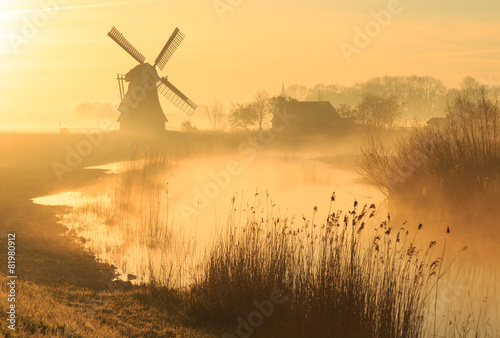 Fotografering  Windmill during a foggy, yellow sunrise in the countryside.