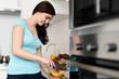 junge frau schneidet melone und kiwi in ihrer küche