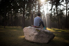Skateboarder Guy Sits On A Rock