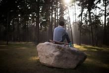 Skateboarder Guy Sits On A Rock