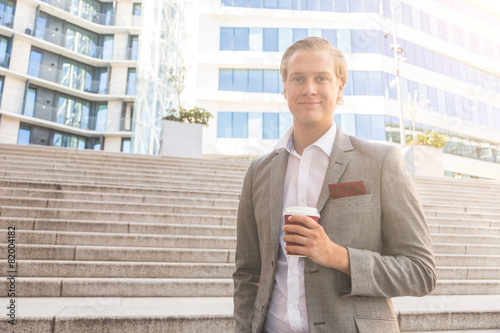 Photo  Fashioned young man in Oslo holding a cup of coffee