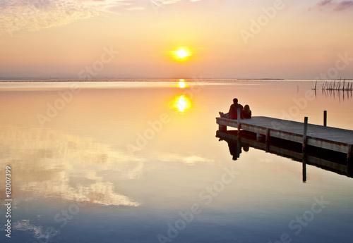 Foto auf AluDibond Pier pareja de novios mirando la puesta de sol