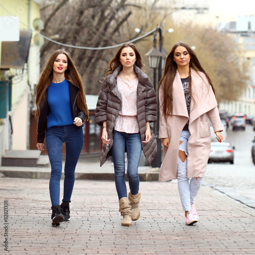 Fotografie, Obraz  Three young beautiful girlfriends in autumn clothes walking on t